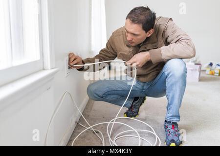 Junger Mann installation Fernsehen Kabel Internet Kabel im Zimmer an der Wand Teppichboden Bodenbeläge, weiße Wände, während Umbau Renovierung, Reinigung, inspectio - Stockfoto