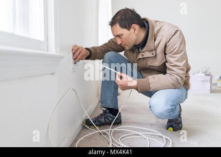 Junger Mann installation Kabelfernsehen Internet Kabel im Zimmer an der Wand Teppichboden Bodenbeläge, weiße Wände, während Umbau Inspektion Sanierung - Stockfoto