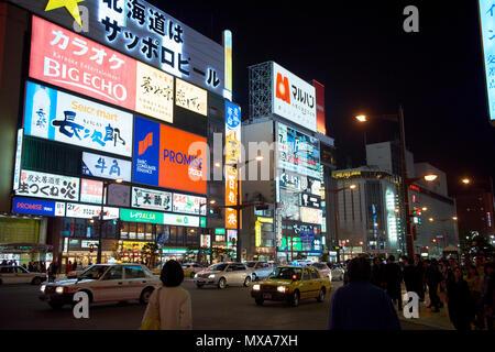 Detail der Leuchtreklamen in der Susukino Bereich in der Nacht in Sapporo, Hokkaido, Japan, mit Straße Verkehr und Fußgänger in der dunklen unten im Bild. - Stockfoto
