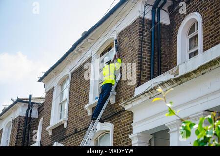 Eine Openreach Ingenieur auf eine Leiter arbeiten an einer Telefonleitung eine Verbindung zu einem Wohnimmobilien. - Stockfoto