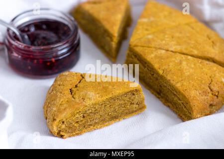 Frisch gebackene Scones mit Kürbis gewürzt Schottische raspberry Marmelade. In Scheiben geschnitten und in einem weißen Leinen Geschirrtuch angezeigt. - Stockfoto