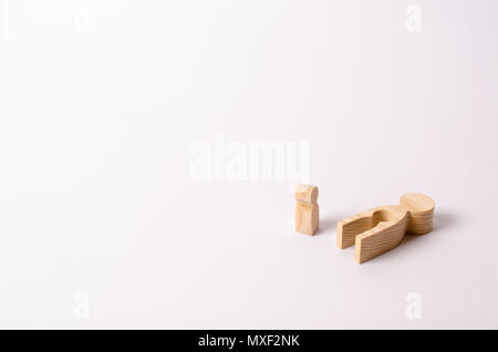 Die Holzfigur des Kindes steht neben Eis seiner Mutter-Creme und es betrachtet. Die Mutter des Kindes starb. Das Konzept der Verlust eines geliebten Menschen - Stockfoto