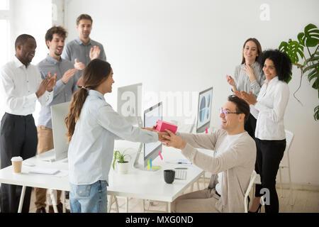 Diverse Kollegen gratulieren männlichen Kollegen mit Geschenkbox - Stockfoto
