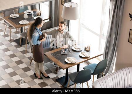 Restaurant Kellnerin serviert Geschäftsmann in modischen herstellen - Stockfoto