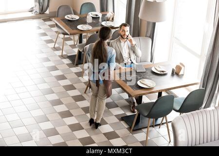 Kellnerin warten, während Kunden am Telefon sprechen - Stockfoto