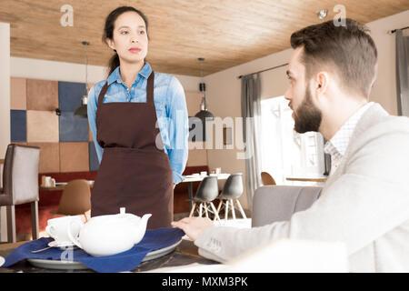 Missfallen Geschäftsmann beschwert Kellnerin über Service - Stockfoto