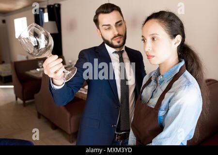 Missfallen restaurateur, schmutzige Weinglas zu Kellnerin - Stockfoto