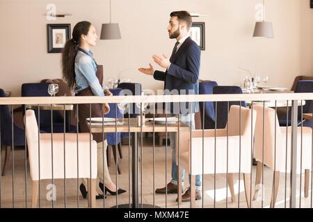 Zuversichtlich Restaurant Manager erklärt Aufgaben Kellnerin - Stockfoto