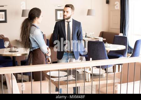 Stirnrunzelnd Gastronom im Gespräch mit Kellnerin - Stockfoto