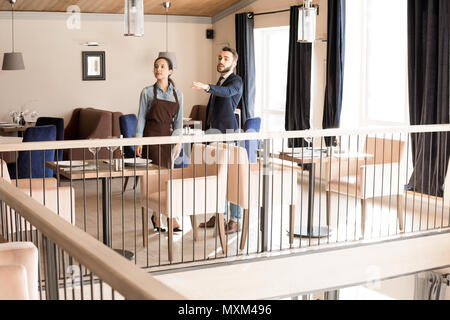 Zuversichtlich manager Vorbereitung restaurant für Veranstaltung mit Kellnerin - Stockfoto
