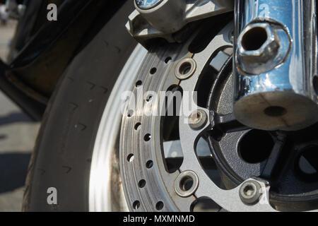 Nahaufnahme der vorderen Rad Motorrad Bremsscheibe. Die Schraube beginnt zu korrodieren, eine Gefahr für die Sicherheit im Straßenverkehr - Stockfoto
