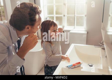 Vater und Tochter Zähneputzen im Badezimmer stehen. Mann seine Tochter, wie die Zähne zu putzen. - Stockfoto