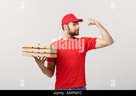 Lieferung Konzept - Portrait von starken stattlichen Delivery man seine Muskeln Durchbiegung und Holding pizza box Pakete. Auf Grau studio Hintergrund isoliert. Kopieren Sie Platz. - Stockfoto