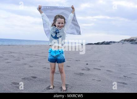 Mädchen mit einem Handtuch in der Wind am Strand - Stockfoto