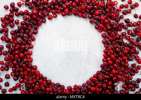 Cherry Vignette, frische Kirschen auf weißem Hintergrund mit einem Kreis verteilt. Gesundes essen Hintergrund Ansicht von oben mit der Kopie. - Stockfoto