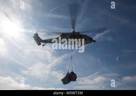 Ein MH-60S Seahawk führt Lieferungen während eines vertikalen Nachschub für den Amphibischen bereit Gruppe Marine Expeditionary Unit Übung Dez. 8, 2016 an Bord der USS Mesa Verde (LPD 19) abgelegt werden. Während der dreiwöchigen Ausbildung evolution, Marines wird eine breite Palette von Maßnahmen und Szenarien die Verbesserung der Interoperabilität und amphibische Kriegsführung Fähigkeiten mit ihren Marine Pendants bekämpfen. Auffüllung auf See ist entscheidend für die bataan Amphibious Ready Gruppe selbst unterstützen, während im Gange. (U.S. Marine Corps Foto von Cpl. Brianna Gaudi) - Stockfoto