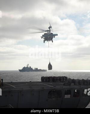 Ein MH-60S Seahawk Hubschrauber liefert cargo Paletten in die USS Carter Hall (LSD 50) aus usns Big Horn (T-AO 198) Dez. 8, 2016, die während der Ausführung einer vertikalen Nachschub während der Amphibischen bereit Gruppe Marine Expeditionary Unit Übung Dez. 8, 2016. Während der dreiwöchigen Ausbildung evolution, Marines wird eine breite Palette von Maßnahmen und Szenarien die Verbesserung der Interoperabilität und amphibische Kriegsführung Fähigkeiten mit ihren Marine Pendants bekämpfen. Auffüllung auf See ist entscheidend für die bataan Amphibious Ready Gruppe selbst unterstützen, während im Gange. (U.S. Marine Corps Foto von gunnery Sgt. Adaecus G - Stockfoto