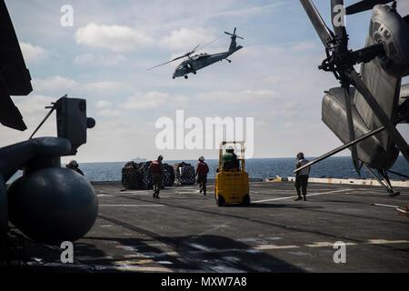 Marines mit dem 24 Marine Expeditionary Unit Hubschrauber support team Erholen liefert sank von einem Sikorsky MH-60S Seahawk an Bord der USS Mesa Verde LPD (19), während eine vertikale Nachschub für den Amphibischen bereit Gruppe Marine Expeditionary Unit Übung Dez. 8, 2016. Während der dreiwöchigen Ausbildung evolution, Marines wird eine breite Palette von Maßnahmen und Szenarien die Verbesserung der Interoperabilität und amphibische Kriegsführung Fähigkeiten mit ihren Marine Pendants bekämpfen. Re-liefert auf See sind lebenswichtig für die bataan Amphibious Ready Gruppe selbst unterstützen, während im Gange. (U.S. Marine Corps Foto von Cpl. - Stockfoto