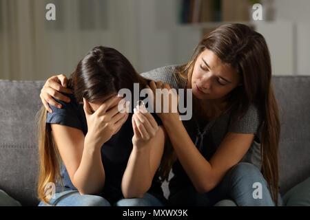 Mädchen trösteten geschieden Freund auf einer Couch im Wohnzimmer zu Hause sitzen - Stockfoto