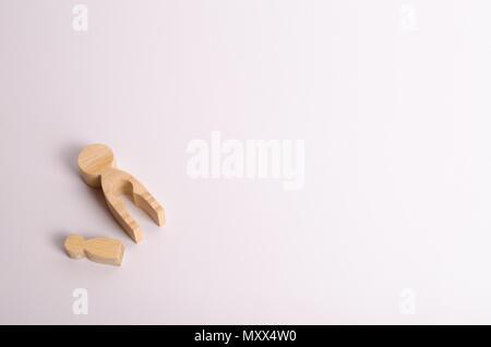 Holz- mutter Zahlen mit einem innen hohl, in der Form eines Kindes und eines Kindes figurine liegen auf einem weißen Hintergrund. Der Begriff der Tragödie, Tod. Fa - Stockfoto