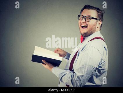 Seitenansicht des gerne mollig Mann lesen interessante Buch lachend und an der Kamera auf grauem Hintergrund - Stockfoto