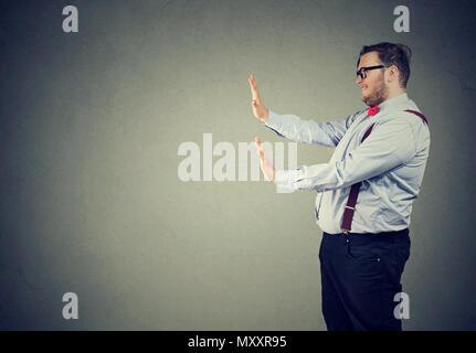 Seitenansicht eines Business Mann in formalen Outfit holding hands up vor sich selbst Druck gegen und versuchen zu stoppen - Stockfoto
