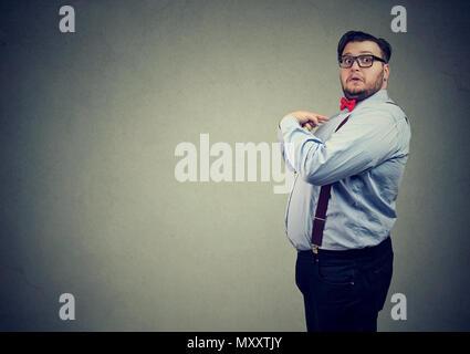 Seitenansicht des mollig Mann in formalen Outfit zeigen sich in der Überraschung verwirrt auf der Suche - Stockfoto