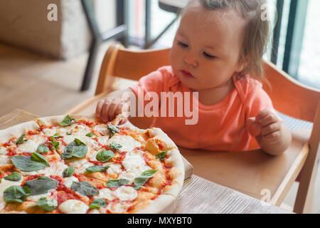 Baby Mädchen essen Pizza im italienischen Restaurant, gesund, ungesundes Essen, Kinder fast food - Stockfoto
