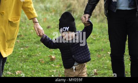 Junge Familie Wandern im Herbst Park mit seinem Sohn, seiner Hand. Glücklich, Mutter, Vater und kleine Mädchen zu Fuß im Herbst Park und Spaß zu haben. Glückliche junge Familie Zeit miteinander zu verbringen, die in der grünen Natur. - Stockfoto