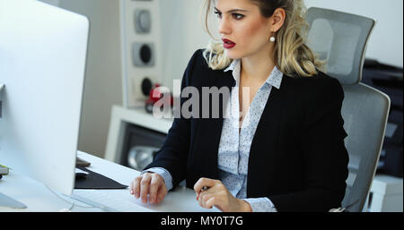 Überarbeitete Geschäftsfrau, die in späten - Stockfoto