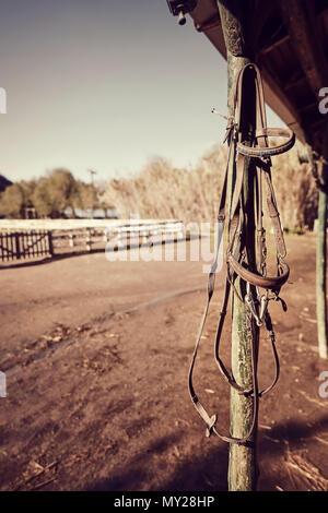 Vintage Leder Pferd Zügel hängen von den Holz- Pol eines Western Horse Farm. Nähe zu sehen. - Stockfoto