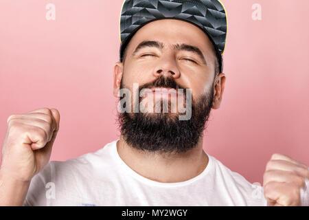 Junge glücklich bärtigen Fußballfan in Gap feiern. emotionale Menschen schreien auf rosa Hintergrund - Stockfoto