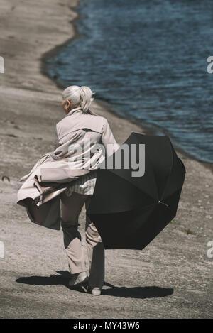Rückansicht der älteren Frau im Mantel Holding schwarz Regenschirm und Wandern am Flußufer - Stockfoto