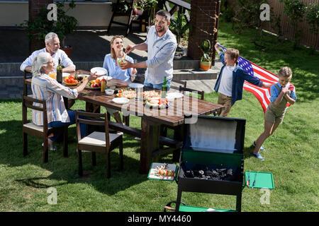 Familie Grill, die während der Feier der 4. Juli, Tag der Unabhängigkeit Konzept - Stockfoto