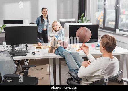 Frauen beobachten, bei der man sich drehende Kugel im Büro - Stockfoto