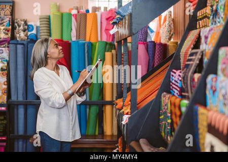 Reifen fabric store Inhaber stehen in Ihrem Shop von bunten Tüchern und Textilien Bestandsaufnahme mit einem Klemmbrett umgeben - Stockfoto