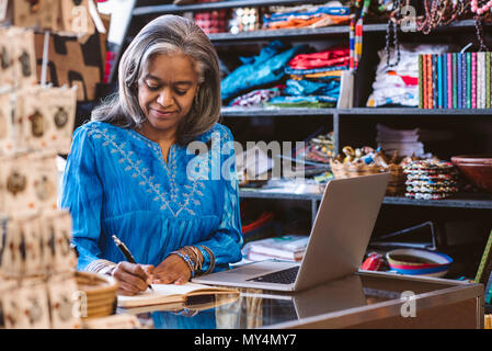 Lächelnd reife Stoff shop besitzer Schreiben in ein Notebook und arbeitet an einem Laptop auf einen Zähler von bunten Tüchern und Textilien umgeben - Stockfoto