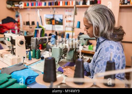 Reifen Näherin sitzt an einer Nähmaschine nähen ein Stück bunten Stoff während der Arbeit allein in ihrer Kleidung workshop - Stockfoto