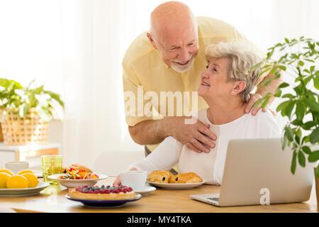 Lächelnd Großvater seiner Frau, die das Internet auf einem Laptop beim Frühstück umarmen - Stockfoto