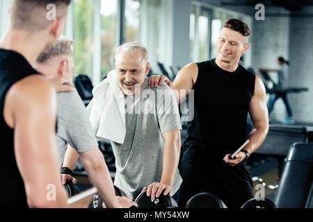 Müde älterer Sportler Training mit Kurzhanteln und Trainer im Fitnessraum - Stockfoto
