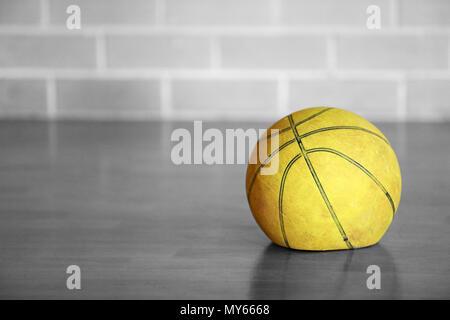 Alte müde abgenutzt Flachbild deflationiert gelb Basketball zuhause auf Holzboden mit Backstein Hintergrund. Glanzlos Leistung. Schwarz und Weiß isoliert Co - Stockfoto