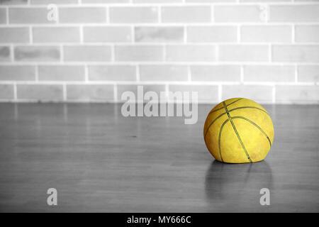 Schwarz und Weiß isoliert Farbe gelb Alt müde Flach deflationiert Basketball lassen. Sie haben keine Energie verwendet, sportliche Ausrüstung getragen. leben. - Stockfoto