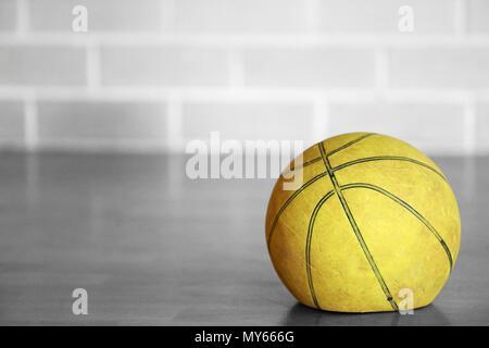Close up Schwarz und Weiß isoliert Farbe Farbe alte müde Stich deflationiert abgenutzt verbrachte Basketball auf einem hölzernen Hofes mit unscharfen brick Hintergrund. - Stockfoto