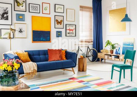 Geräumiges Wohnzimmer mit einer Decke und orange Kissen auf ein blaues Sofa, grünen Stuhl, bunten Teppich und Galerie der Plakate und Gemälde auf Weiß - Stockfoto