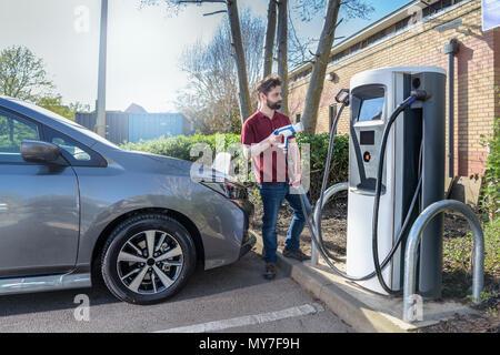 Fahrlehrer aufladen elektrischen Auto am Parkplatz Ladestation - Stockfoto