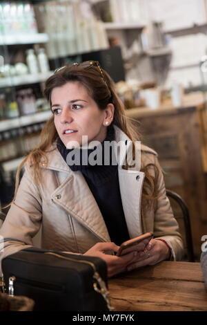 Junge Frau im Cafe Tabelle holding Smartphone