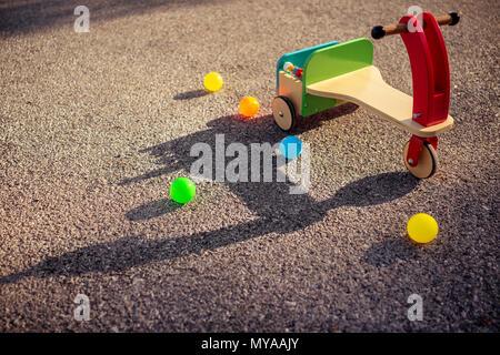 Stilvolle vintage Holz- bunte Fahrrad und viele kleine Kugeln auf dem Asphalt, im Freien Unterhaltung für Kinder, glückliche Kindheit Konzept - Stockfoto