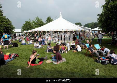 Menschen entspannten Sitzen und Liegen auf dem Boden lesen außerhalb von Festzelt auf dem Hay Festival Website in Sunshine 2018 Hay-on-Wye Wales UK KATHY DEWITT - Stockfoto