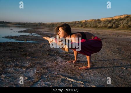 Yoga Frau am Strand bei Sonnenuntergang. - Stockfoto