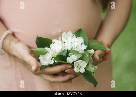 Schwangere Frau mit dunklen Haaren in rosa mit weißen Blumen auf grünem Gras Hintergrund - Stockfoto